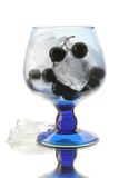 Black currant in the wineglass with an ice. Black currant in the blue wineglass with an ice isolated on white background Stock Images