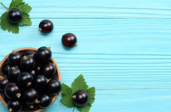 Black currant in wooden bowl with green leaf on blue wooden background Royalty Free Stock Images