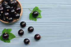 Black currant in wooden bowl with green leaf on blue wooden background Stock Photos
