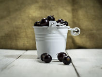 Black currants in a bucket on white wooden background Royalty Free Stock Images