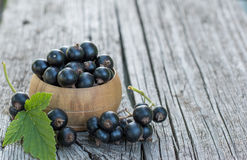 Black Currants. Fresh ripe organic black currants with green leaf in a wooden bowl on the rustic wooden table. Closeup with copy space Royalty Free Stock Photos