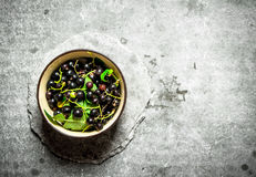 Black currants with leaves in the Cup. Royalty Free Stock Photography