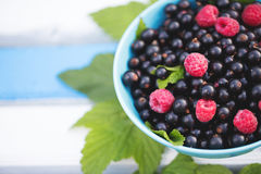 Black currants and raspberries with leaves. Black currants and raspberries with leaves in a cup on a wooden background Royalty Free Stock Image