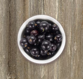 Black currants in a white ceramic bowl. Top view. Ripe and tasty currants on a wooden background Stock Photos