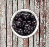 Black currants in a white ceramic bowl. Top view. Ripe and tasty currants on a wooden background. Black currants on wooden table with copy space Stock Photos