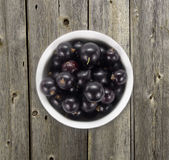 Black currants in a white ceramic bowl. Top view. Ripe and tasty currants on a wooden background. Black currants on wooden table with copy space Royalty Free Stock Images