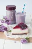 Black current cheesecake slice near bilberry milkshake and lilac Stock Photo