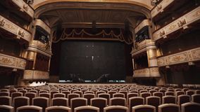 Black curtain defending scene in luxurious empty opera hall. Chairs rows, red cushions and drapes, gold decorations on balcony stock video footage