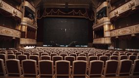 Black curtain defending scene in magnificent empty concert hall. Chairs rows, red cushions and drapes, gold decorations on balcony stock footage