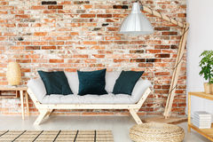 Black cushions on sofa. Black decorative cushions placed on bright wooden sofa next to oversize lamp stock images