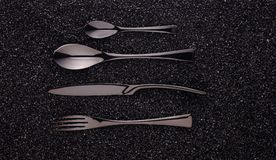 Black cutlery set. On the black background Stock Photography