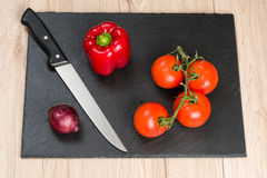 Black cutting board with knife and vegetables, ready for slicing Stock Image