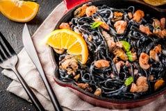 Black cuttlefish ink pasta with seafood. Modern italian dinner, Mediterranean food, black cuttlefish ink spaghetti pasta with seafood, olive oil and basil,  on Royalty Free Stock Image