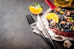 Black cuttlefish ink pasta with seafood. Modern italian dinner, Mediterranean food, black cuttlefish ink spaghetti pasta with seafood, olive oil and basil,  on Stock Images