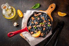 Black cuttlefish ink pasta with seafood. Modern italian dinner, Mediterranean food, black cuttlefish ink spaghetti pasta with seafood, olive oil and basil,  on Royalty Free Stock Images