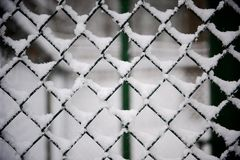 Black Cyclone Fence Covered With Snow Royalty Free Stock Images