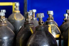 Black cylinders with oxygen are at the factory in the shop, close-up. Storage stock images