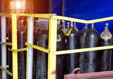 Black cylinders with oxygen are at the factory in the shop, a sunset is breaking through the window, cylinders. Black cylinders with oxygen are at the factory in royalty free stock photos