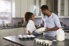 Black dad and young daughter look at each other while baking Stock Photos