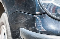 Black damaged car in crash accident with scratched paint and dented rear bumper metal body, close up selective focus.  Royalty Free Stock Photos