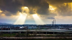 Black dark rainy clouds over the polluted urban dense city with two big holes in the clouds royalty free stock images