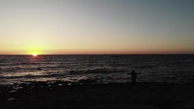 Black dark silhouette of person standing on a beach with arms wide open looking towards sunset over ocean with small boat on horiz stock video footage
