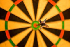 Black Dart Pink Attach on Yellow Green and Red Dart Board Royalty Free Stock Photos
