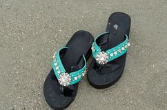 Black decorated flip flop. On the beach royalty free stock photo