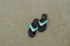 Black decorated flip flop. On the beach royalty free stock photos