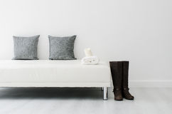 Black decorative pillows on a white casual sofa. In the living room with boot and candle Royalty Free Stock Photo
