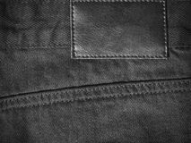 Black denim textile for background back closeup with leather label Royalty Free Stock Photography