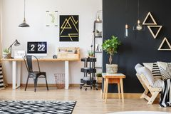 Creative workspace with triangle motive. Black designer chair at table with lamp and wooden organizer in creative workspace with triangle motive stock photos