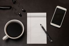 Black desk with coffee in white cup, notebook, white smartphone and pen flat lay/ Work-space concept with black and white royalty free stock photography