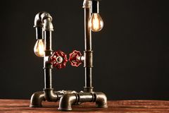 Black desk lamp made of water pipes and gauge pressure meter.  Royalty Free Stock Photography