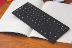 Black desktop wireless keyboard on the note Royalty Free Stock Photos