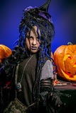 Black devilry. Little girl in a costume of witch posing with pumpkins over dark background Royalty Free Stock Photography