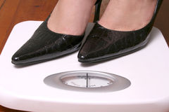 Black diagonal stilletoes on scale Stock Photography