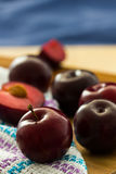 Black Diamond plums (grown in Portugal) with cloth on wooden board. Whole fruits and cut pieces Stock Images