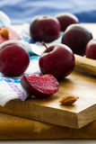 Black Diamond plums on wooden board with cloth and knife. Whole fruits, cut pieces and pits Royalty Free Stock Photos