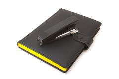 Black diary (notebook) and black stapler. On a white background royalty free stock images