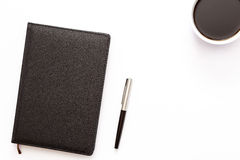Black diary, pen and a Cup of black coffee on a white background. Minimal a working concept for your desktop. Stock Image