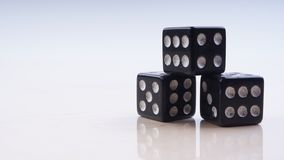 Black dice with white dots isolated on white background. Selective focus stock images