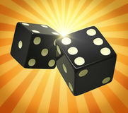 Black dice in yellow orange beams Stock Photos