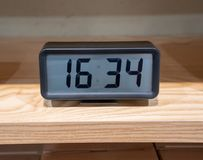 Black digital clock with metal stand on wooden shelf royalty free stock photo