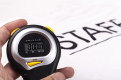 Staff Timing. Black digital stopwatch held in hand on white background with staff writing stock images