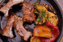 Black dinner plate with barbequed ribs, sweet peppers, and squash salad. Black dinner plate with barbequed ribs, grilled sweet peppers, and squash salad with royalty free stock photo