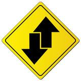 Black directional arrow sign. Two way traffic black directional arrows illustrated on yellow highway caution sign Royalty Free Stock Photography