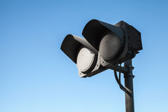 Black dirty double traffic lights switched off over blue sky Royalty Free Stock Photo