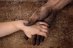 Black dirty man hands holding kid clean hand Royalty Free Stock Images