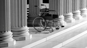 Black disability wheelchair, with ancient pillars Royalty Free Stock Image
